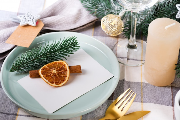 Festliches weihnachts- und des neuen jahresdetailsgedeck mit trockener orange und zimt auf einem grauen gewebe. essplatz eingerichtet