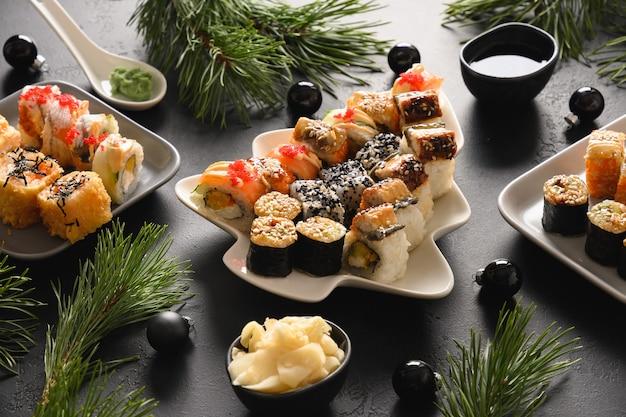 Festliches weihnachtsessen mit sushi mit weihnachtsdekoration auf schwarzem tisch. nahansicht. neujahrsparty.