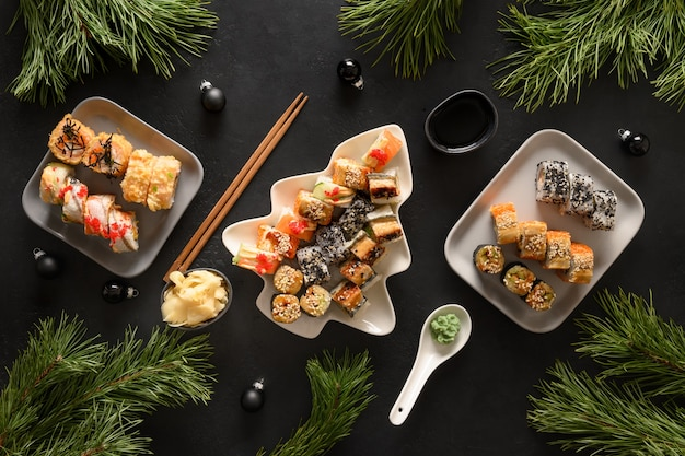 Festliches weihnachtsessen mit sushi-set mit weihnachtsdekoration auf schwarz. neujahrsparty.