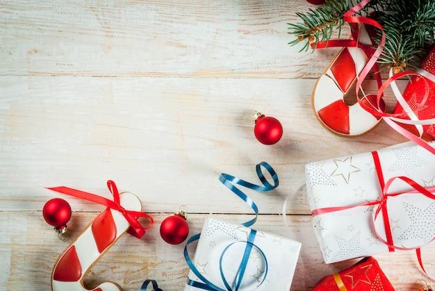 Festliches weihnachtshölzerner weißer hintergrund, mit weihnachtsbaumasten, kiefernkegeln, dekorationen, weihnachtsgeschenken und lebkuchen, draufsichtkopienraum