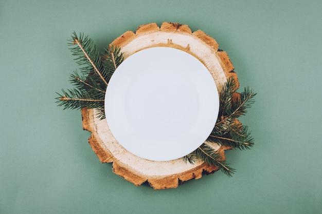 Festliches weihnachtsnatürliches artgedeck mit weißer platte auf holzschnittplatten