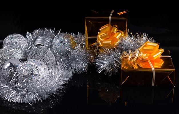 Festliches weihnachtsstillleben mit silbernen dekorationen und lametta und zwei luxuriösen goldgeschenken, die mit schleifen auf dunklem hintergrund mit exemplar verziert sind