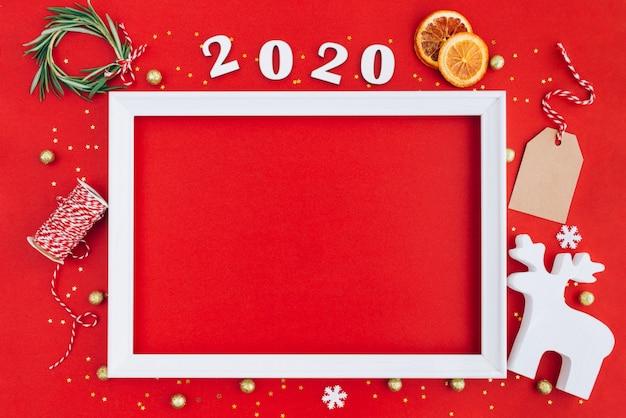 Festliches weihnachtsweißer rahmen gemacht von den weihnachtsdekorationen und von 2020 hölzernen ziffern auf rotem hintergrund mit kopienraum.