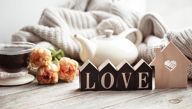 Festliches zuhause stillleben mit blumen, einer tasse tee und dekor details auf einer holzoberfläche nahaufnahme.