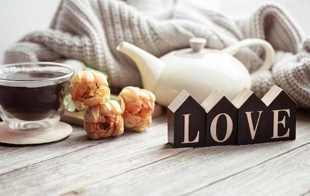 Festliches zuhause stillleben mit blumen, einer tasse tee und einer teekanne auf einer holzoberfläche hautnah.