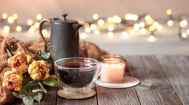 Festliches zuhause stillleben mit einer tasse getränk, blumen und dekor details auf einem unscharfen hintergrund mit bokeh.