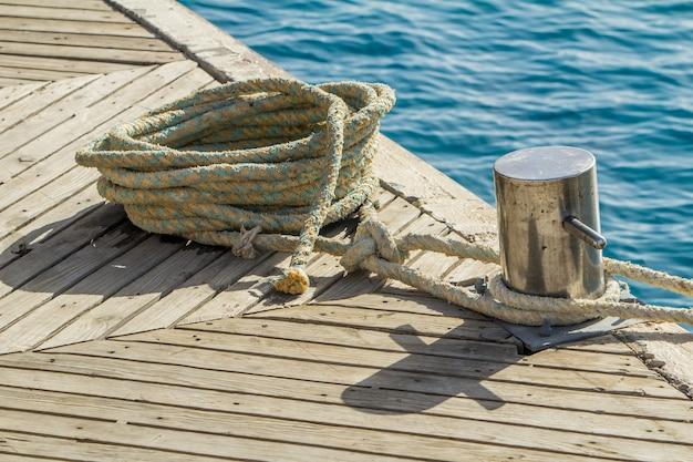 Festmachenseil und schiffspoller auf meerwasser- und yachehintergrund