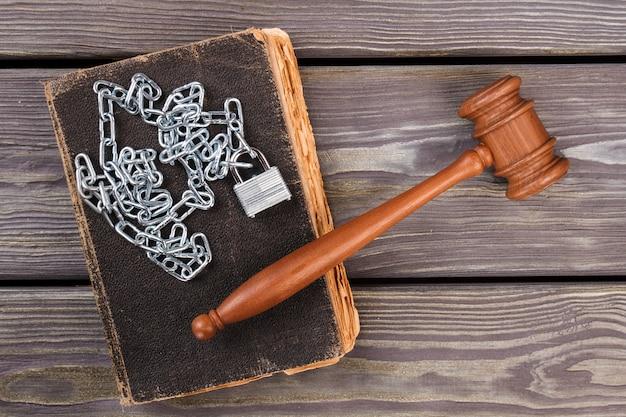 Festnahme und bestrafung konzept flach liegen. holzhammer mit ketten und altem abgenutzten buch.