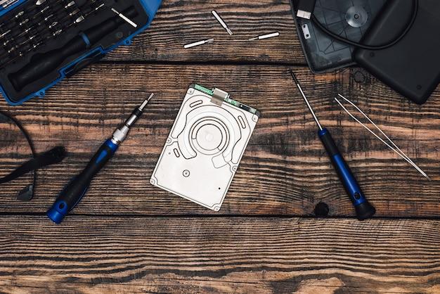 Festplatte mit professionellem präzisionsschraubendreher und einigen werkzeugen auf holztisch