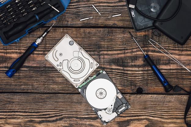 Festplatte mit schraubendreher und anderen werkzeugen auf holztisch