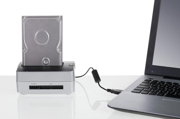 Festplattenlaufwerk mit dockingstation an einen laptop angeschlossen. zur datenspeicherung.