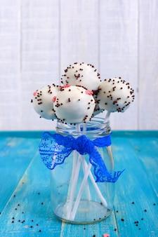 Festtagsleckereien. cake pops. kekskuchen in der weißen schokoladenglasur auf einem hellen blauen hölzernen hintergrund. vertikale ansicht.