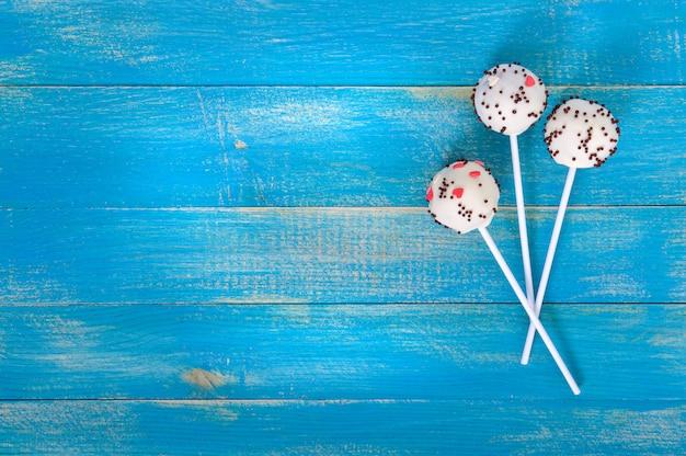 Festtagsleckereien. cake pops. kekskuchen in der weißen schokoladenglasur auf einem hellen blauen hölzernen hintergrund.
