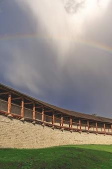 Festungsmauer auf dem hintergrund eines regenbogens und eines bewölkten himmels natürliches licht