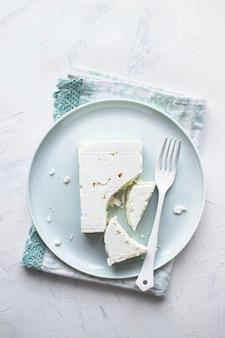 Feta-käse auf einem weißen teller mit gabel flach legen