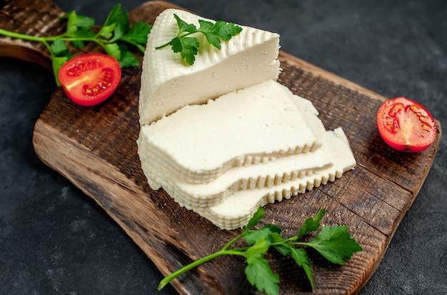 Feta-käse mit kirschtomaten auf einem schneidebrett