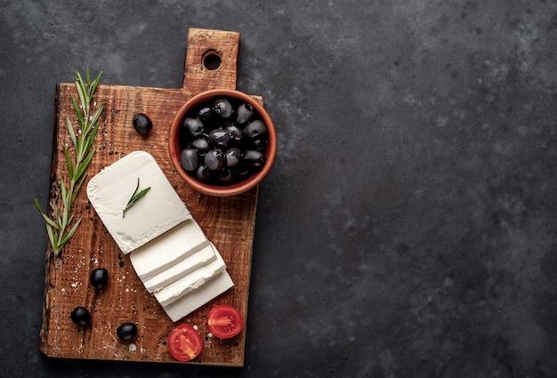 Feta-käse, mit rosmarin, tomaten, oliven auf einem steinhintergrund. draufsicht mit speicherplatz für ihren text