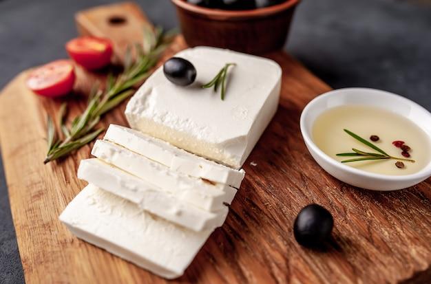 Feta-käse, mit rosmarin, tomaten, oliven auf einem steinhintergrund.