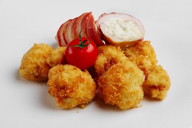 Feta-käse mit speck umwickelt und in öl mit kartoffeln in panade gebraten