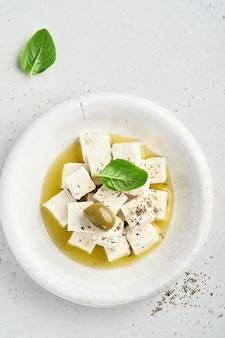 Feta-käsewürfel mit rosmarin, oliven und olivenöl auf hellgrauer oberfläche.
