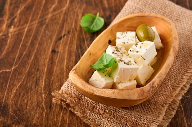 Feta-käsewürfel mit rosmarin, oliven und olivenöl auf holzoberfläche.