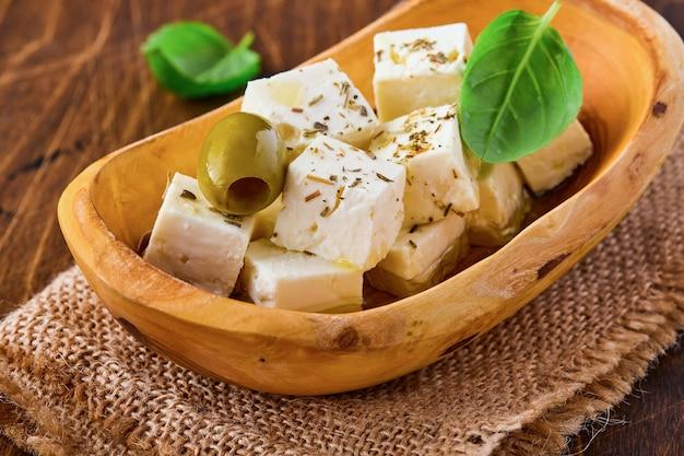 Feta-käsewürfel mit rosmarin, oliven und olivenölsauce in einer schüssel