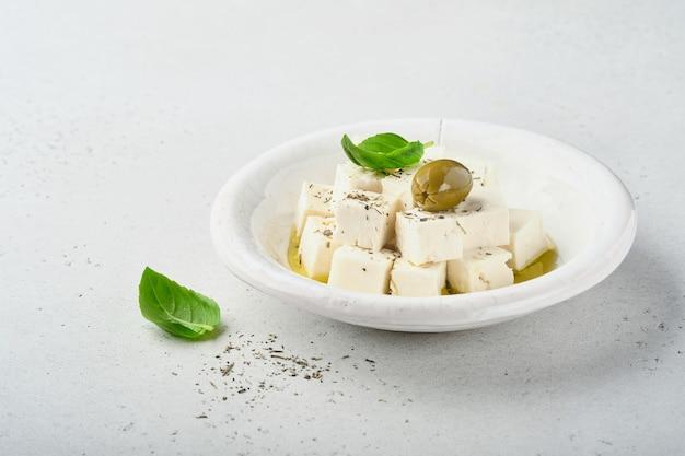 Feta-käsewürfel mit rosmarin, oliven und olivenölsauce in weißer schüssel auf hellgrauem hintergrund
