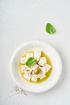 Feta-käsewürfel mit rosmarin, oliven und olivenölsauce in weißer schüssel