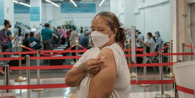 Fette ältere frau muss coronavirus-covid-schulter mit verband impfen, der miniherz zeigt