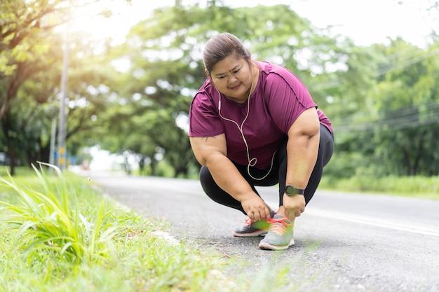 Fette asiatische frau, die schnürsenkel im freien bindet und sich bereit macht, zu laufen, trainiert für das konzept der gewichtsverlustidee.