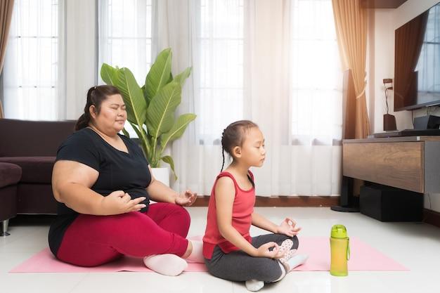 Fette asiatische frau mit kleinem mädchen, das zu hause trainiert, sport- und erholungsideenkonzept.