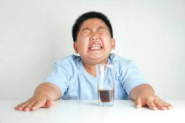 Fette asiatische kinder, die alkoholfreie getränke trinken