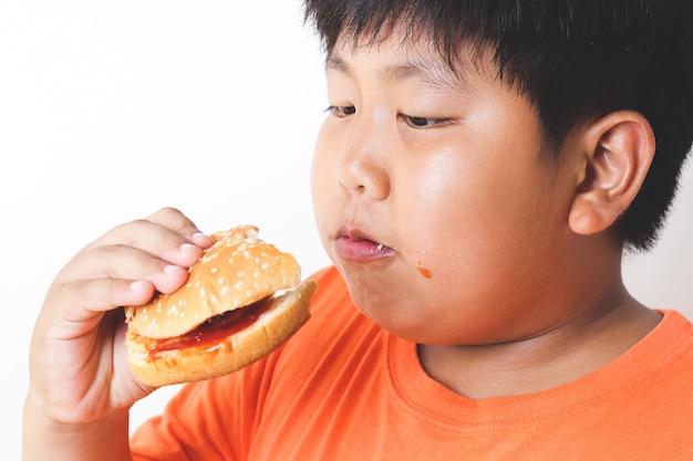 Fette asiatische kinder essen hamburger. lebensmittelkonzepte, die bei kindern körperliche gesundheitsprobleme verursachen.