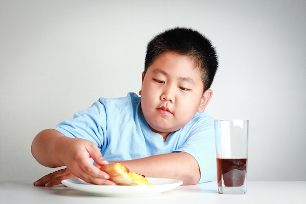 Fette asiatische kinder essen pizza auf einem weißen tisch mit sodanektar. weißer hintergrund. konzepte zur gewichtskontrolle von kindern
