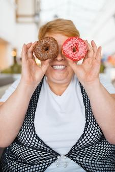 Fette frau, die donuts statt augen im einkaufszentrum hält, ungesundes essen. übergewichtige weibliche person am tisch mit junk-dinner, fettleibigkeitsproblem