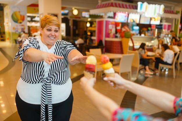 Fette frau, die eiscreme, fastfood-restaurant kauft