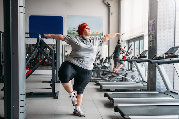 Fette frau, die gleichgewichtsübung im fitnessstudio tut. kalorien brennende, fettleibige weibliche person beim training im sportverein