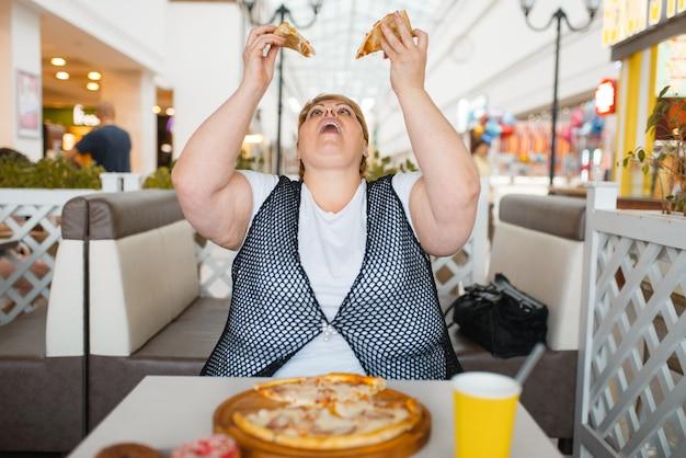 Fette frau, die pizza im einkaufszentrumrestaurant isst, ungesundes essen. übergewichtige weibliche person am tisch mit junk-dinner, fettleibigkeitsproblem