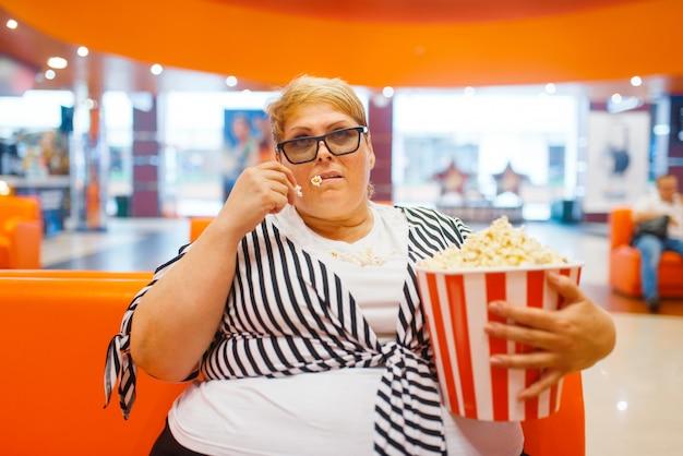 Fette frau, die popcorn im kinosaal isst, ungesundes junk-food. übergewichtige weibliche person im einkaufszentrum, fettleibigkeitsproblem