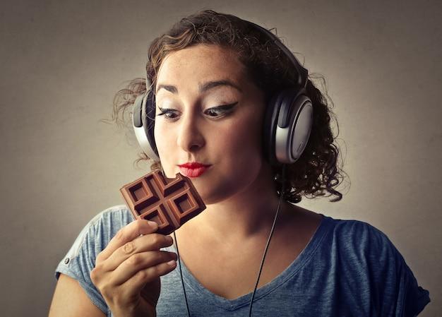 Fette frau, die schokolade isst und musik hört