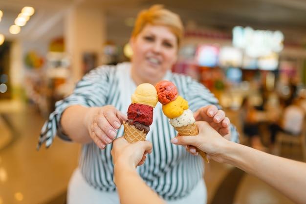 Fette frau, die zwei eiscreme im fastfood-einkaufszentrum restaurant kauft. übergewichtige weibliche person mit eis, fettleibigkeitsproblem
