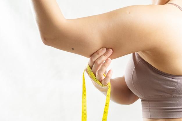 Fette frau, frauenhand, die auf ihrem übermäßigen fetten arm mit maßband, frau diät-lebensstilkonzept kneift