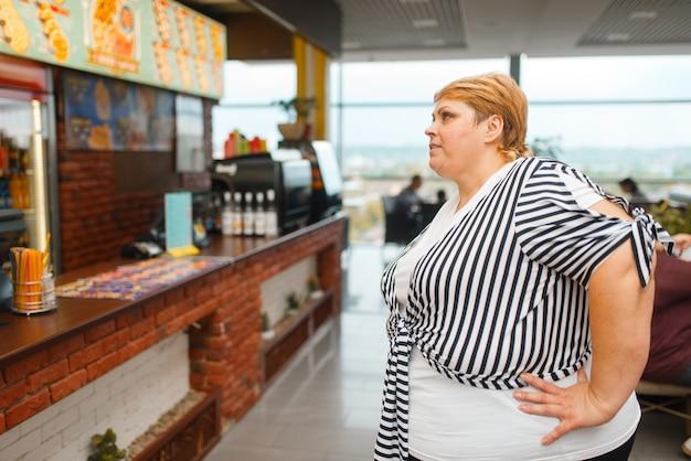 Fette frau im fast-food-restaurant-menü. übergewichtige weibliche person, die fastfood kauft, fettleibigkeitsproblem