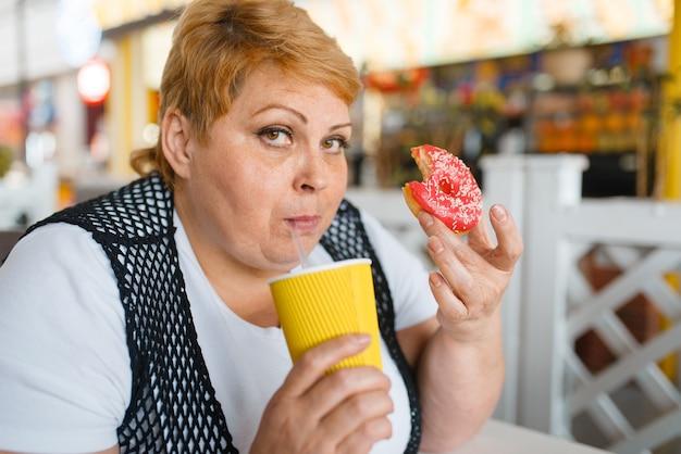 Fette frau isst donuts im fastfood-restaurant, ungesundes essen. übergewichtige weibliche person am tisch mit junk-dinner, fettleibigkeitsproblem