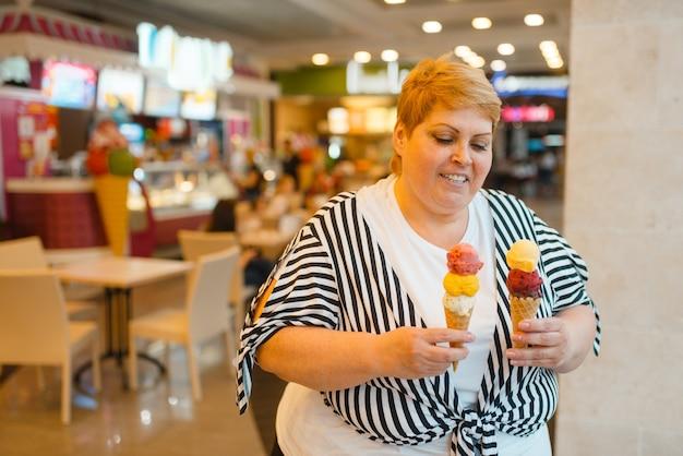 Fette frau mit eis im fastfood-mall-restaurant, ungesundes essen. übergewichtige weibliche person mit eiscreme, fettleibigkeitsproblem