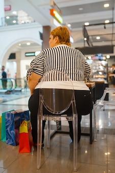 Fette frau sitzt am tisch im fastfood-restaurant, rückansicht. übergewichtige weibliche person im fastfood-einkaufszentrum, fettleibigkeitsproblem