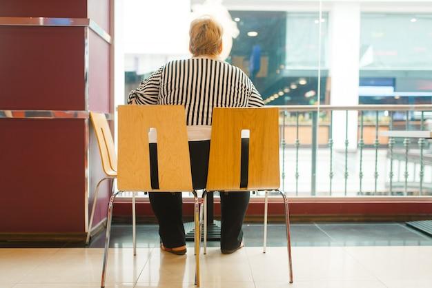 Fette frau sitzt auf zwei stühlen im fastfood-restaurant, rückansicht. übergewichtige weibliche person im fastfood-einkaufszentrum, fettleibigkeitsproblem
