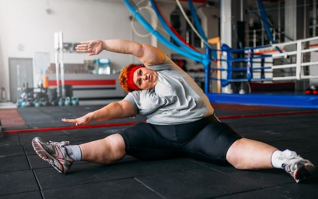 Fette frau übungen auf dem boden, training im fitnessstudio. kalorien brennen, fettleibige weibliche person, training im sportverein
