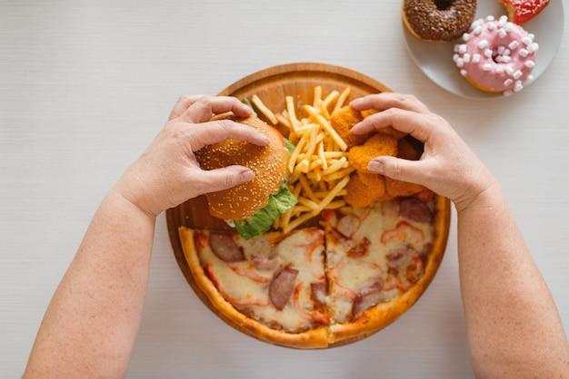 Fette frauenhände gegen kalorienreiches essen. übergewichtige weibliche person am tisch mit junk-dinner, fettleibigkeitsproblem, ungesunde ernährung