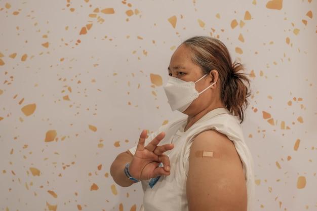 Fette frauenschulter mit verbandshand, die ok zeigt, ist gegangen, um coronavirus covid zu impfen